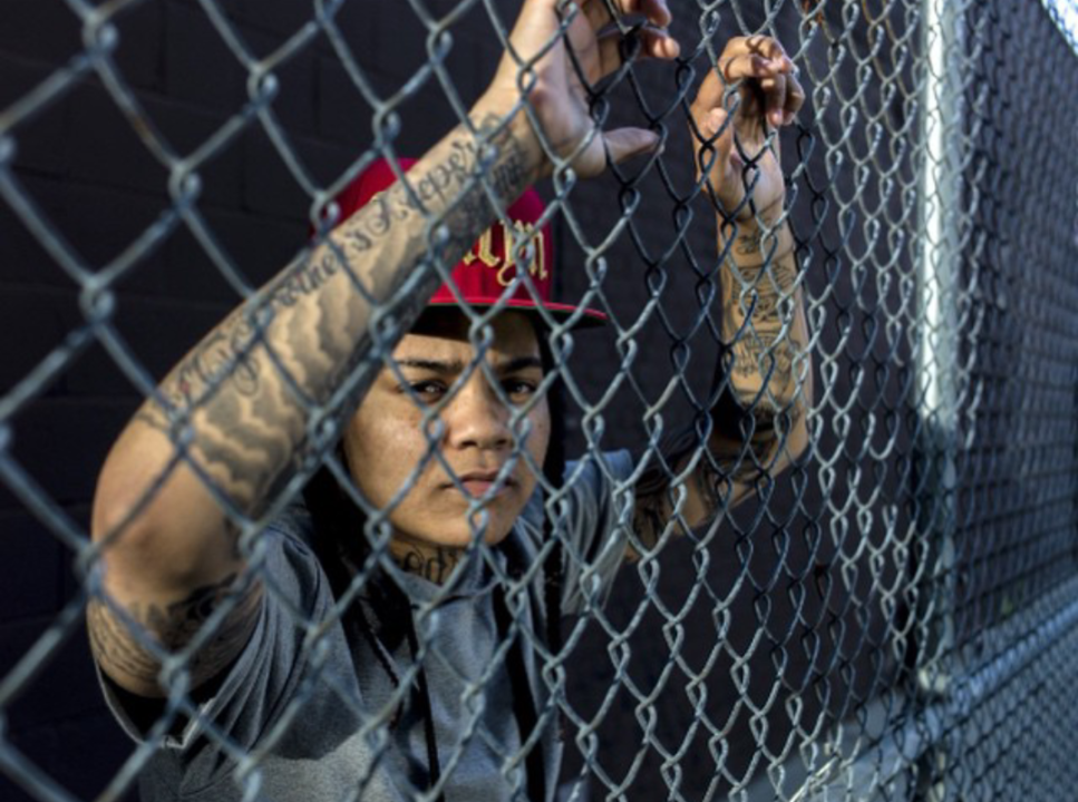 Young M.A poses with hands on fence photoshoot
