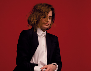 christine and the queens poses on red background in white and black suit