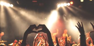 Woman holding up heart sign in crowd looking at performances on stage